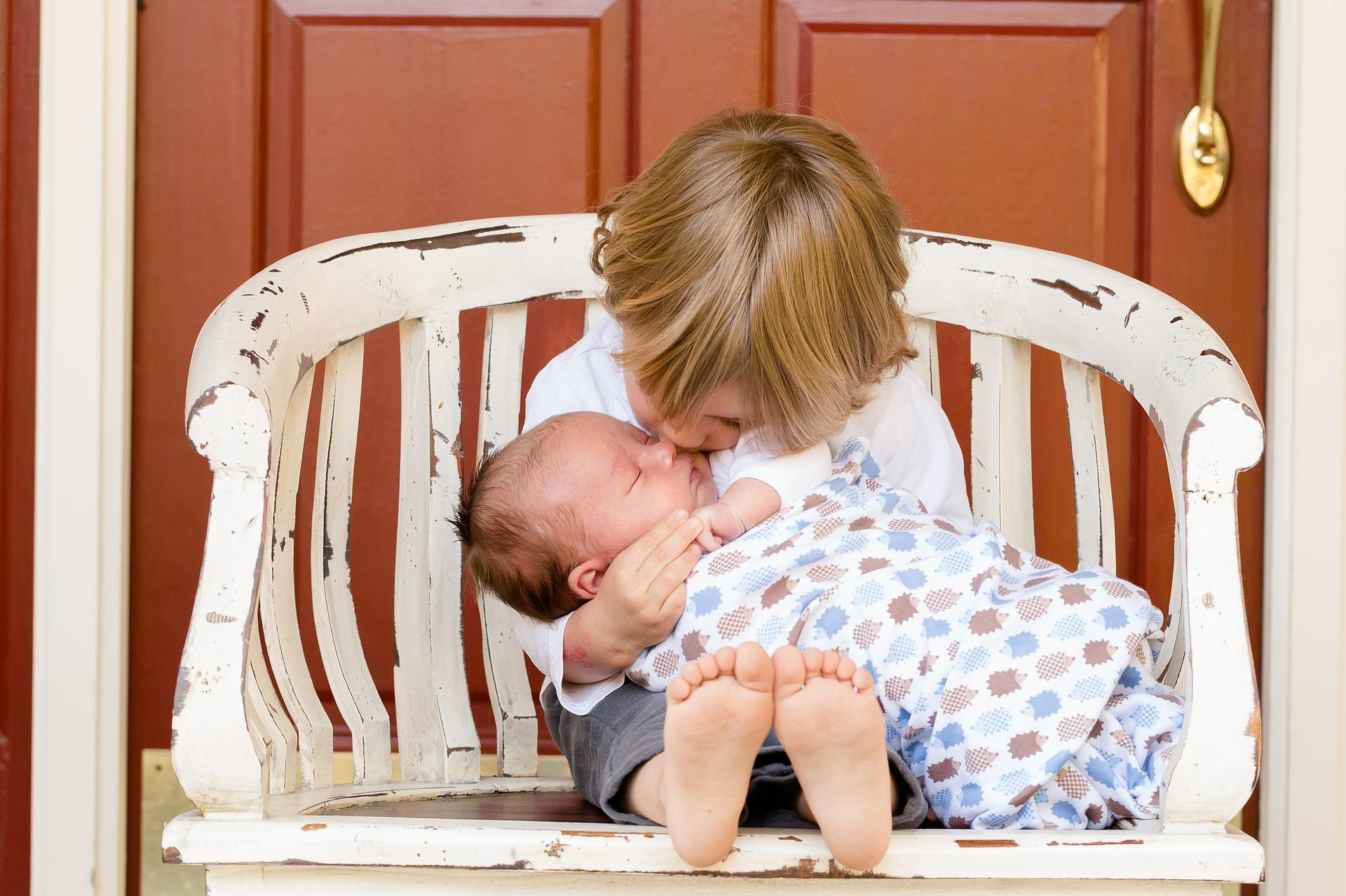 sestra-drži-bebu-u-krilu-i-ljubi-je